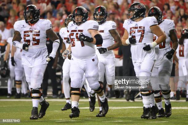 Offensive lineman Jaypee Philbert Jr #55 and offensive lineman Jacob Still and offensive lineman Troy Elliot of the Arkansas State Red Wolves lead...