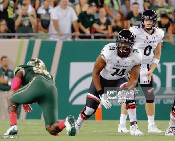 Offensive lineman Kendall Calhoun of the Cincinnati Bearcats and teammate quarterback Hayden Moore scan the South Florida Bulls defense during the...
