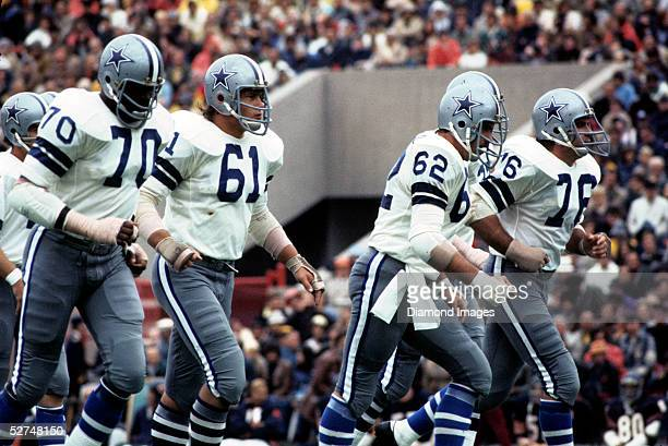 Offensive lineman Rayfield Wright Blaine Nye John Fitzgerald and John Niland of the Dallas Cowboys jog to the line of scrimmage for the next play...