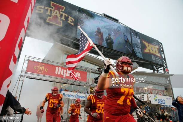 Offensive lineman Sean Foster of the Iowa State Cyclones takes the field carrying the American flag before game action against the Kansas Jayhawks at...