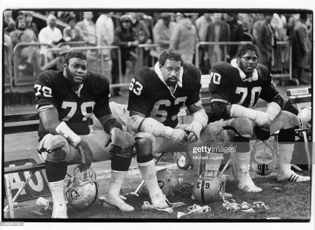 Offensive linemen Art Shell Gene Upshaw and Henry Lawrence of the Oakland Raiders sit on the bench against the Minnesota Vikings at Oakland Alameda...