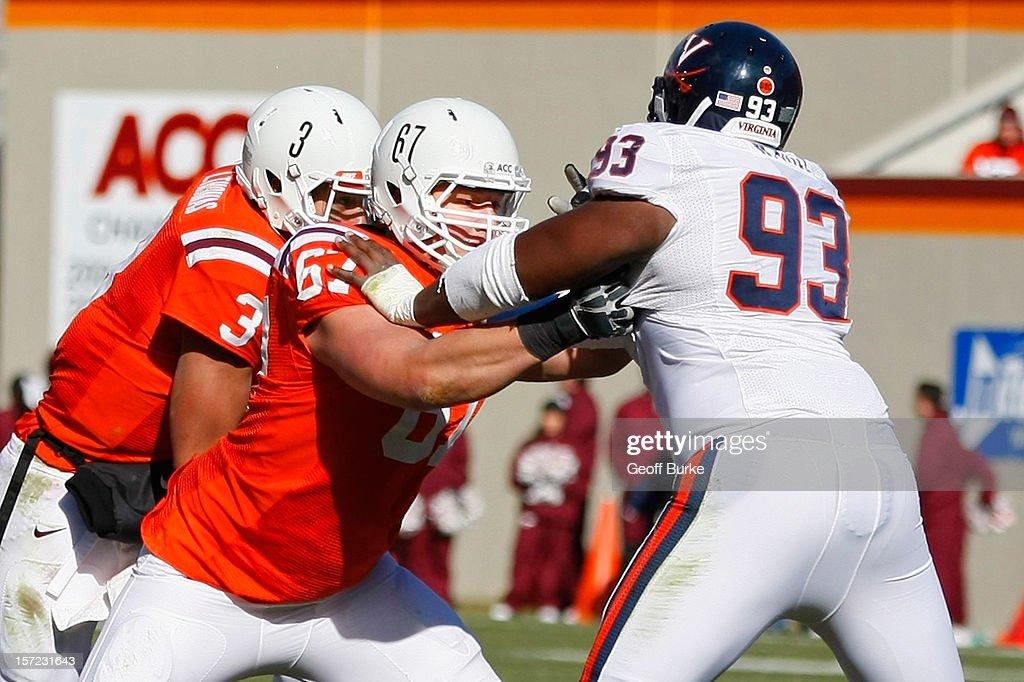 Offensive tackle Michael Via #67 of the Virginia Tech Hokies blocks defensive tackle Will Hill #93 of the Virginia Cavaliers at Lane Stadium on November 24, 2012 in Blacksburg, Virginia.