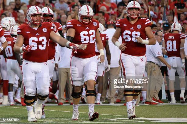 Offensive tackle Tanner Farmer and offensive tackle Cole Conrad and offensive lineman Nick Gates of the Nebraska Cornhuskers enter the field during...