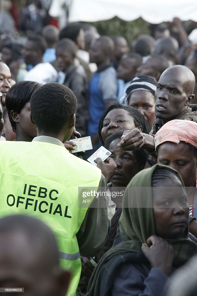 A IEBC offical checks the registration papers of voters who are queuing at the the Kisumu Social Centre, one of the largest polling stations in Kisumu town in western Kenya March 4, 2013. Kenyans go to the polls March 4, 2013 for the first time since bloody post-poll violence five years ago for which a top presidential candidate faces trial for crimes against humanity. Neck-and-neck rivals for the presidency, Prime Minister Raila Odinga and his deputy Uhuru Kenyatta, have publicly vowed there will be no repeat of the bloodshed that followed the disputed 2007 polls in which over 1,100 people died and some 600,000 were displaced. AFP PHOTO / Till MUELLENMEISTER