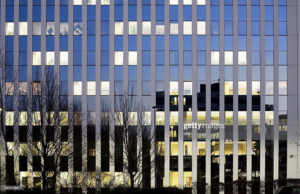 Office building at dusk, illuminated windows : Stock Photo