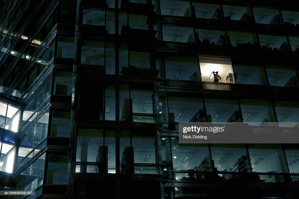 Office building at night, man standing in one illuminated window, low angle view
