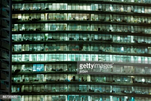 Office building with lights on at night : Stock Photo