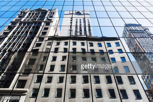 Office buildings reflected in modern glass facade