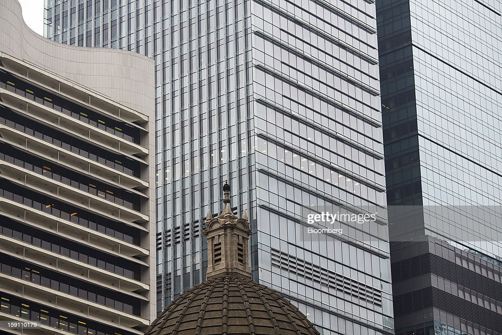 Office buildings stand behind the dome of the Legislative Council Building in the central business district of Hong Kong, China, on Friday, Jan. 4, 2013. Hong Kong topped the ranks as the most expensive office market by total occupancy cost, according to a report by CBRE Research released on Jan. 7. Photographer: Jerome Favre/Bloomberg via Getty Images