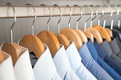 Shirts hanging on wooden hangers ordered by colour - zoomed on the collars