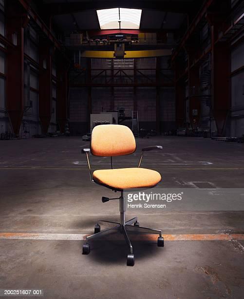 Office chair under spotlight in empty warehouse