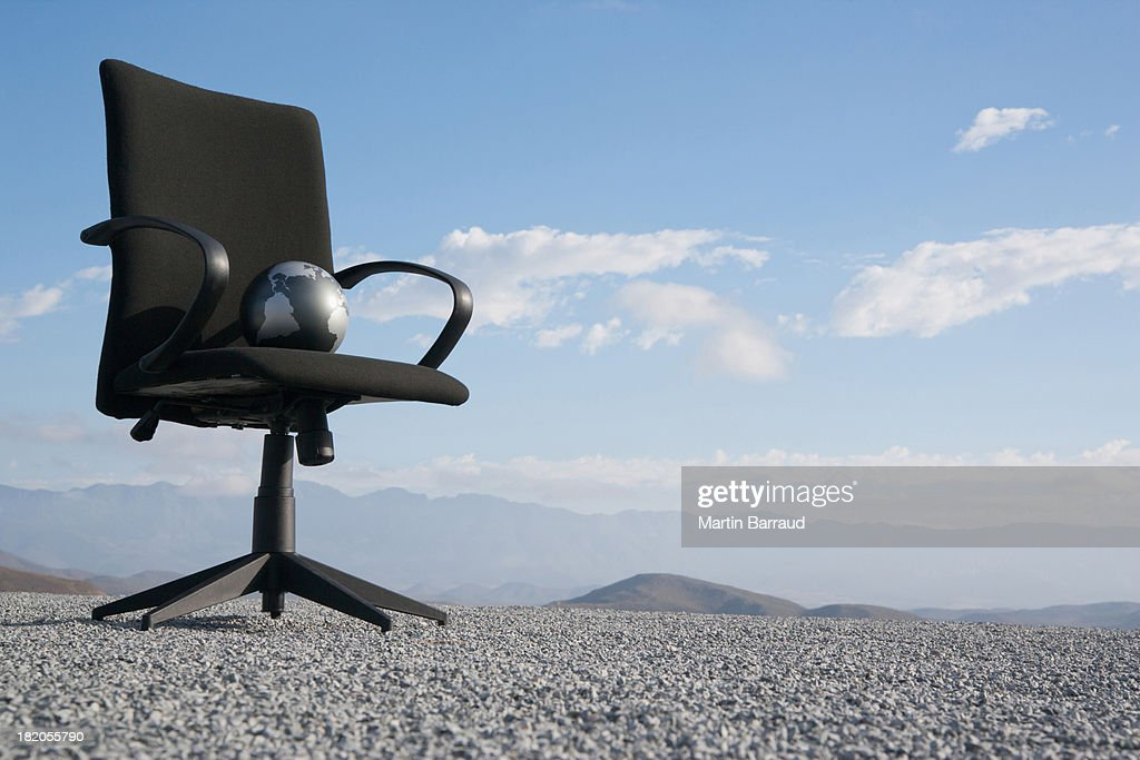 Office chair with globe on a terrain full of pebbles