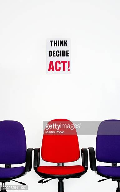 Office chairs beneath 'THINK DECIDE ACT!' sign
