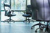 Office chairs in a board room by a sunny window.