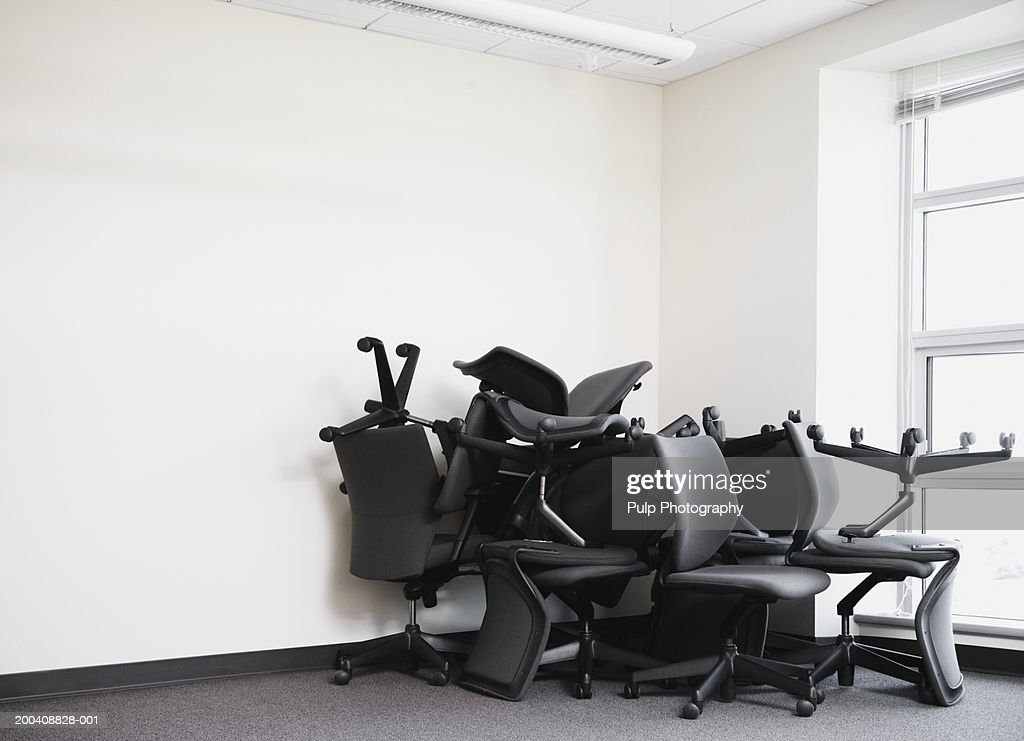 Office chairs piled in corner of empty office