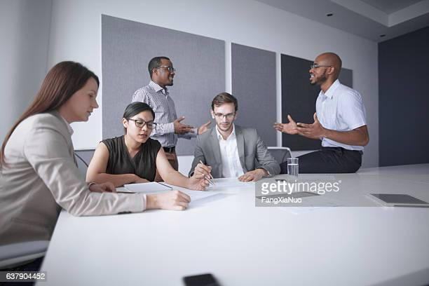 Office colleagues conversing in business meeting