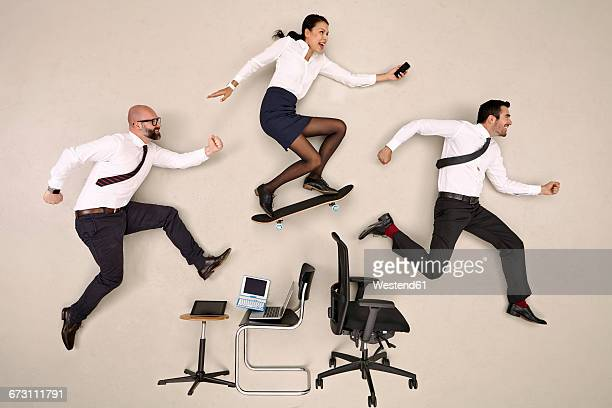 Office colleagues jumping and skatboarding over chairs and devices