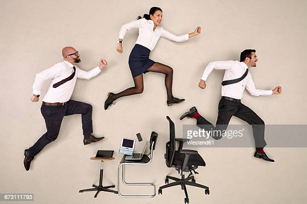 Office colleagues jumping over chairs and devices