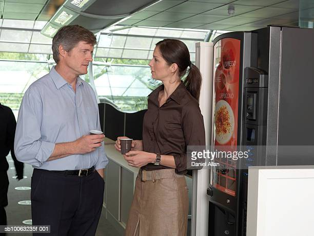 Office colleagues standing next to coffee machine in office, talking