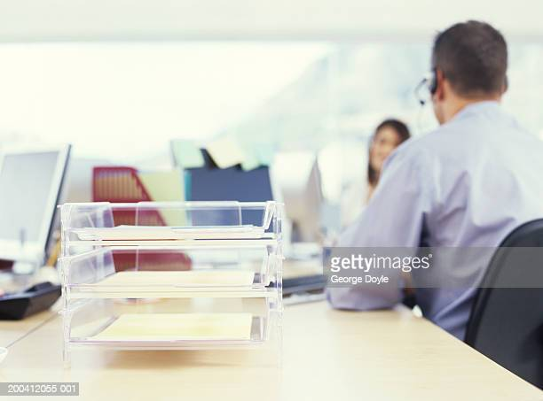 Office colleagues talking, in and out filing tray on desk