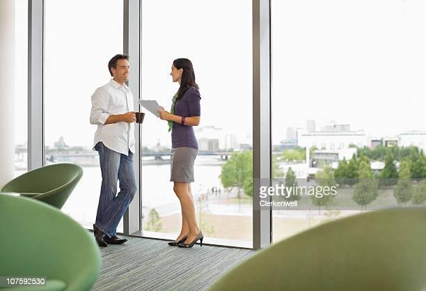 couple debout près de fenêtre discuter sur la baie
