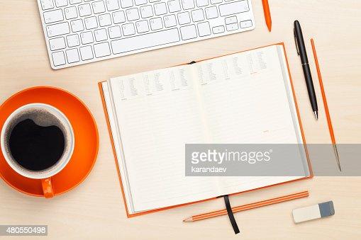 Mesa de oficina con ordenador de sobremesa, suministros y una taza de café : Foto de stock