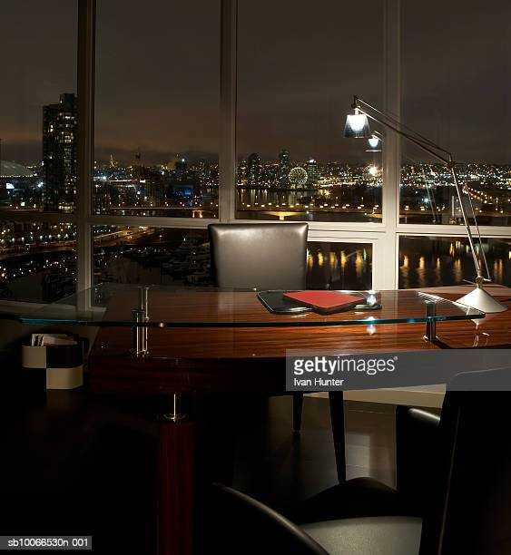 Office desk with illuminated lamp at night