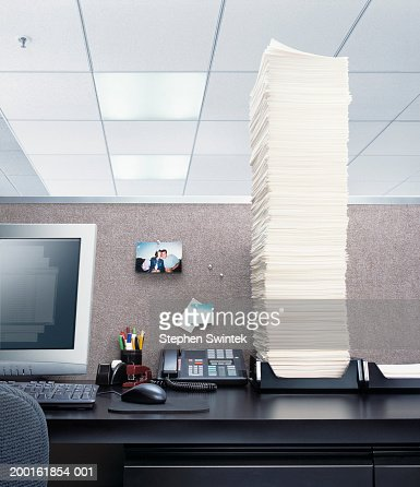 Office desk with papers piled high in 'In' box : Stock Photo
