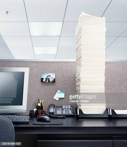 Office desk with papers piled high in 'In' box