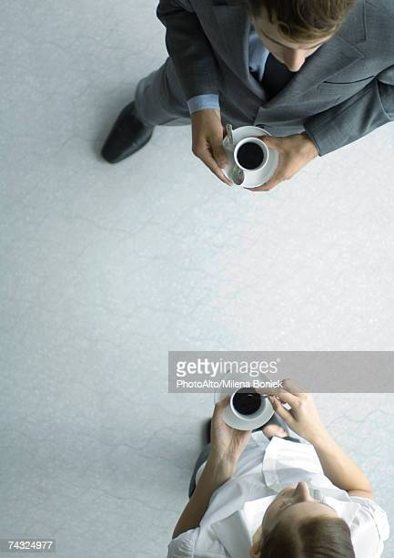 Office employees standing with coffee cups, view from directly above