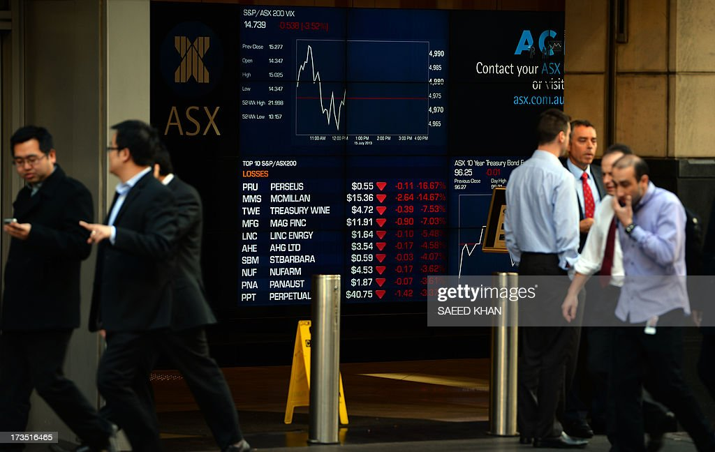 Office employees walk in front of an electronic screen at the Australian Stock Exchange (ASX) in Sydney on July 16, 2013. Australian Prime Minister Kevin Rudd on July 16 announced the country's divisive fixed-price carbon tax will be scrapped a year ahead of schedule in favour of a market-driven emissions trading scheme. AFP PHOTO / Saeed KHAN
