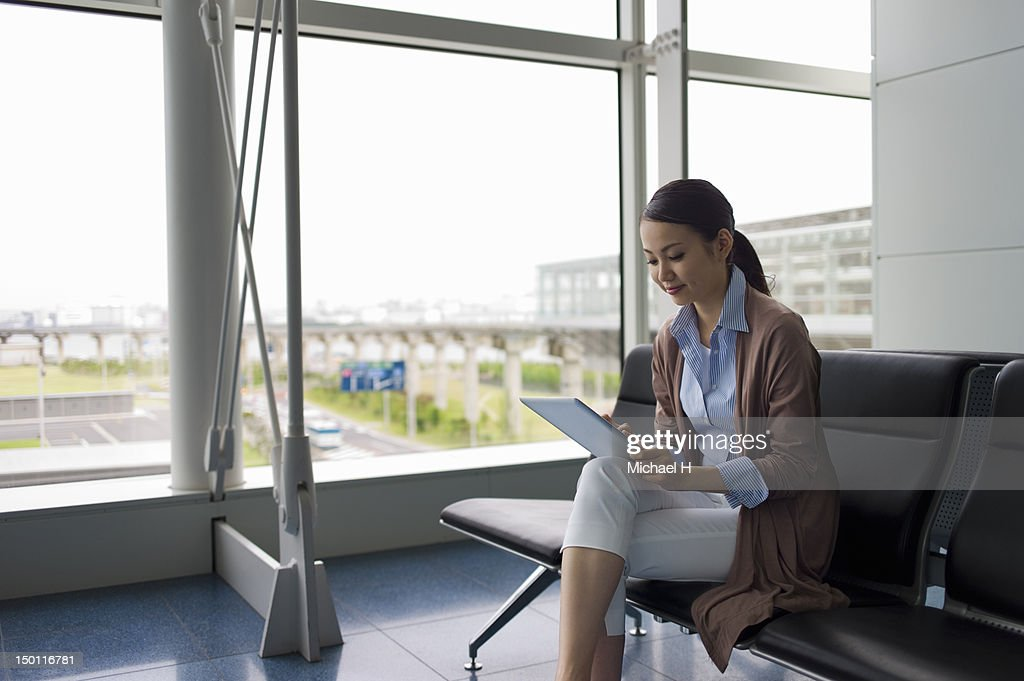 Office lady checking her e-mail at an airport : Stock Photo