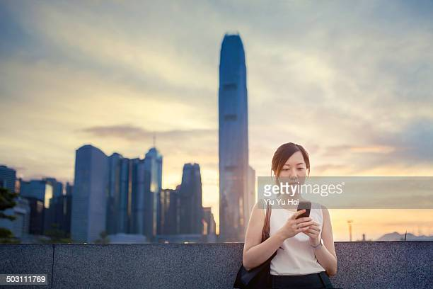 Office lady standing against cityscape and texting