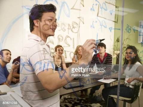 Office leader explaining writing on the glass wall : Stock Photo