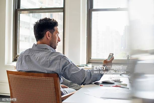 Office life. A man at a desk checking his phone.