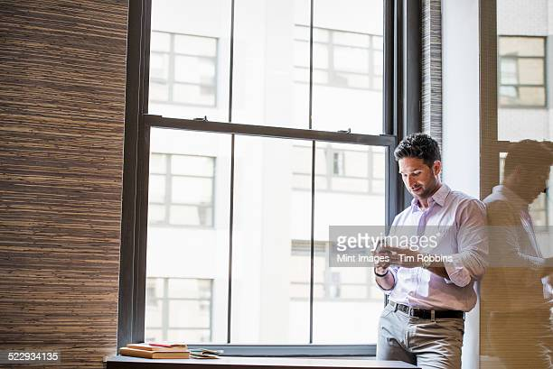 Office life. A man in an office checking his smart phone.