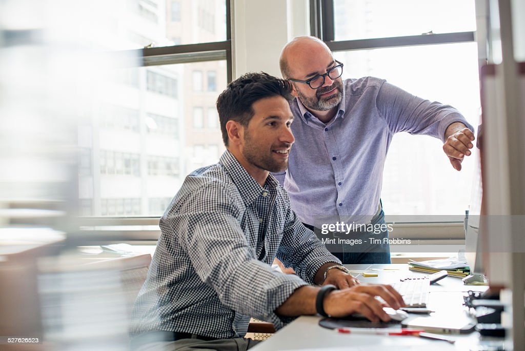 Office life. Two men in an office, using a computer screen.