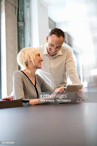 Office life. Two people sharing a digital table in an office.