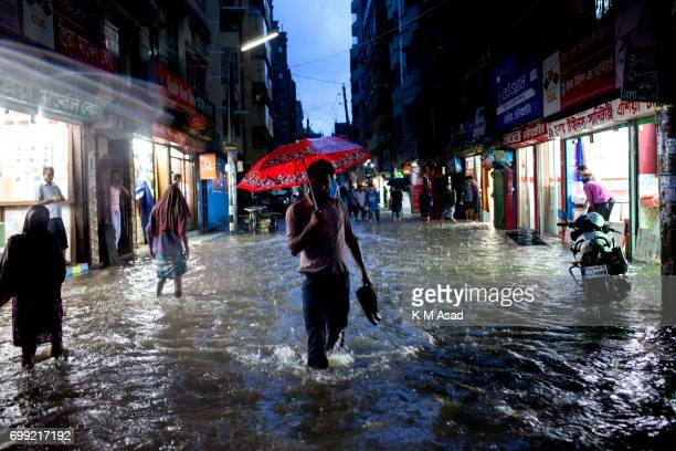 OLD DHAKA DHAKA BANGLADESH A office man with umbrella walk in the rain water when heavy rainfall made waterlogging in Dhaka city The death toll rises...