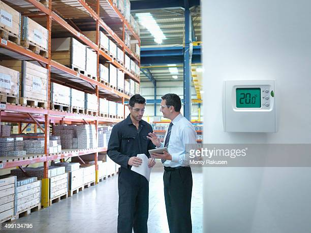Office manager and worker discuss energy use near thermostat in factory