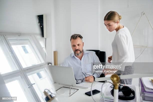 Office Manager arbeiten mit Kollegen diskutieren, beim Blick auf seinen Computer
