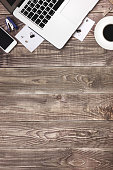 Office objects. Open laptop, notebook, mobile phone, pen and cup of coffee on a wooden background. Top view, space for text