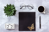 Office or home table desk. Wooden cubes calendar May 22. Black notepad, cup of coffee, succulent, glasses on marble background Concept stylish workplace Flat lay Top view