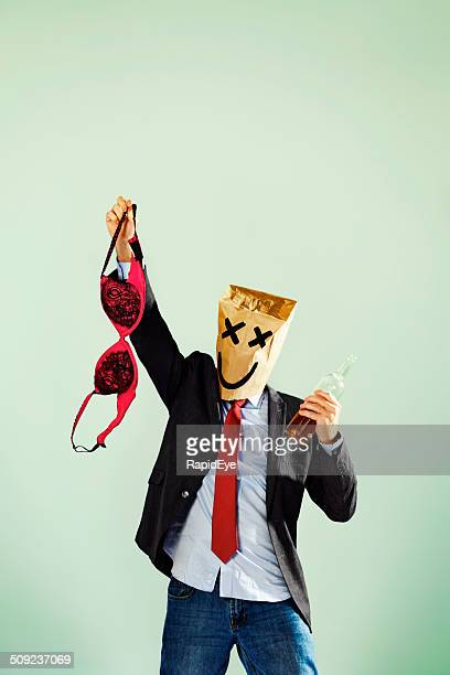 Office party drunk in paper-bag mask waving bra