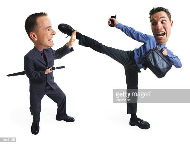 office quarrel errupts as two caucasian business men in shirts and ties fight as one kicks high into the air