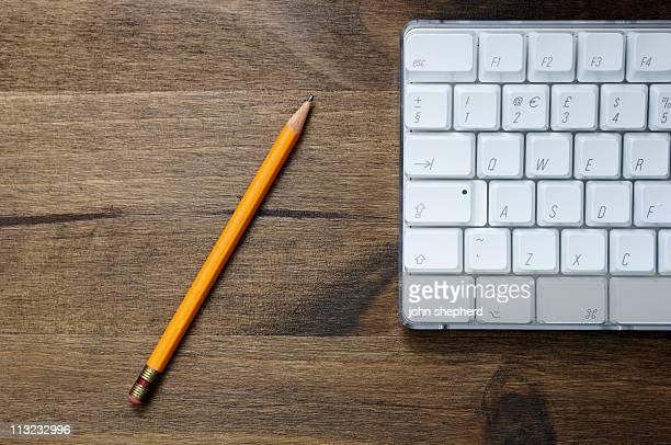 Office scenario,  pencil and computer keyboard against dark oak