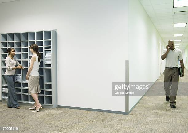 Office scene, two women talking by mailboxes while man using cell phone walks through hallway