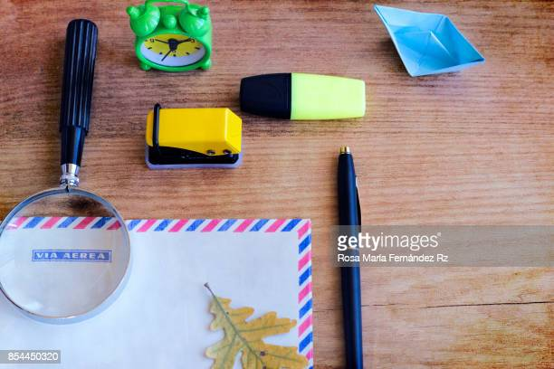 Office supplies. Magnifying glass, envelope, paper boat, oak leaf, alarm clock, pen, stapler and marker on wwoden table background.  High angle view and copy space