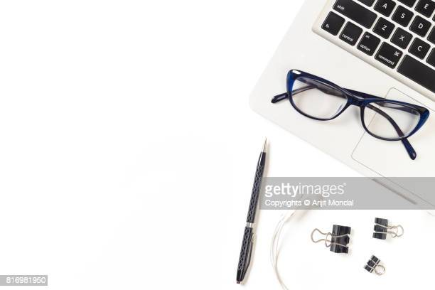 Office table top view clean lay with laptop, eye wear, pen, earphone, office clips copy space