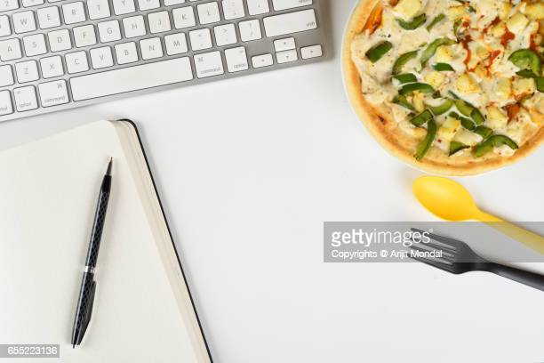 Office table top view of pizaa, computer keyboard, fork, spoon, notebook and pen